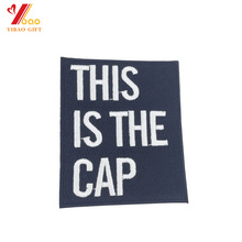 Cheap custom fabric embroidery white color letter sew on merrow border patch for hats or clothing