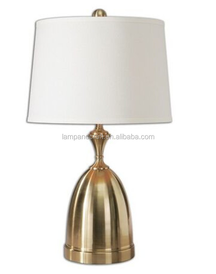 Metal turnings finished in a plated brushed brass decorative desk lighting with white linen fabric tapered round hardback shade