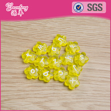 Wholesale cheap letter printed yellow flower plastic beads bulk for garment