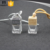 square shape wooden cap glass handing empty car perfume bottle