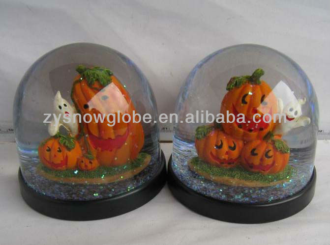 Plastic ghost and pumpkin snow globe