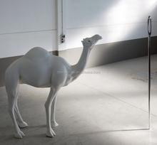 Large white fiberglass life size camel statue with staring needle eye