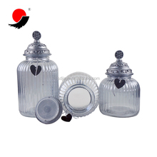 Clear glass storage jar with airtight metallic lid and string heart decoration