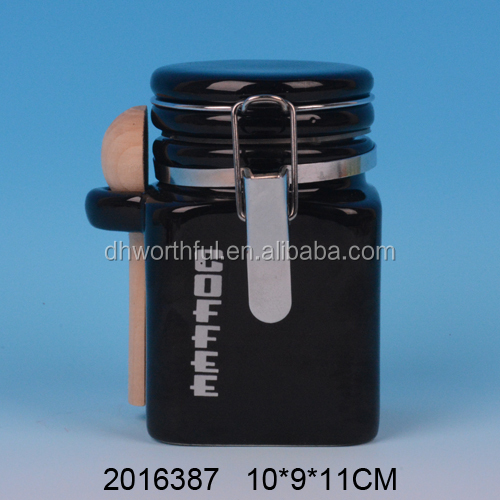 Handmade black ceramic coffee canister with wooden spoon