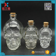 Hot selling different size liquor whiskey glass bottle skull head shaped wine glass vodak bottle with stopper