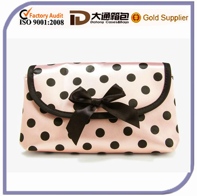 Expandable cosmetic bag features polka dot pattern and hidden magnetic button closure