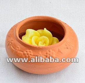Rose candle in a clay Thai water jar.