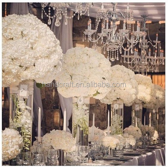 Centerpiece flower arrangement with white orchids cascading over the side dripping crystal beads and roses