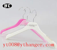 Pink plastic clothes hanger patent over store hook hanger