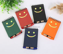 Recycled paper notebook with sticky notes and smiling face cover