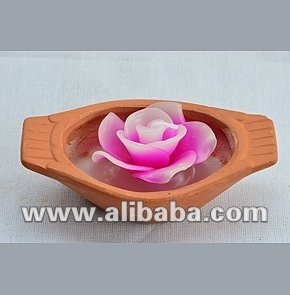 Rose candle in a clay Thai paddling boat