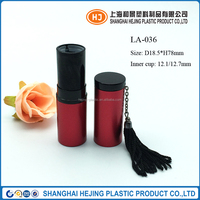 Empty red aluminum lipstick tube container with tassel