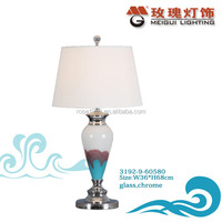 white and chrome table lamp in glass