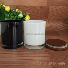 Black cylinder glass candle holder and white glass candle jar with wood lid