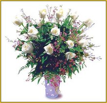 White Roses arranged in a glass vase with greens