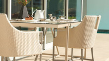 Graceful home patio furniture for dinner time with glass top table and sleek high legged chair rattan dining set