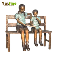 Boy and girl reading book on bench bronze sculpture
