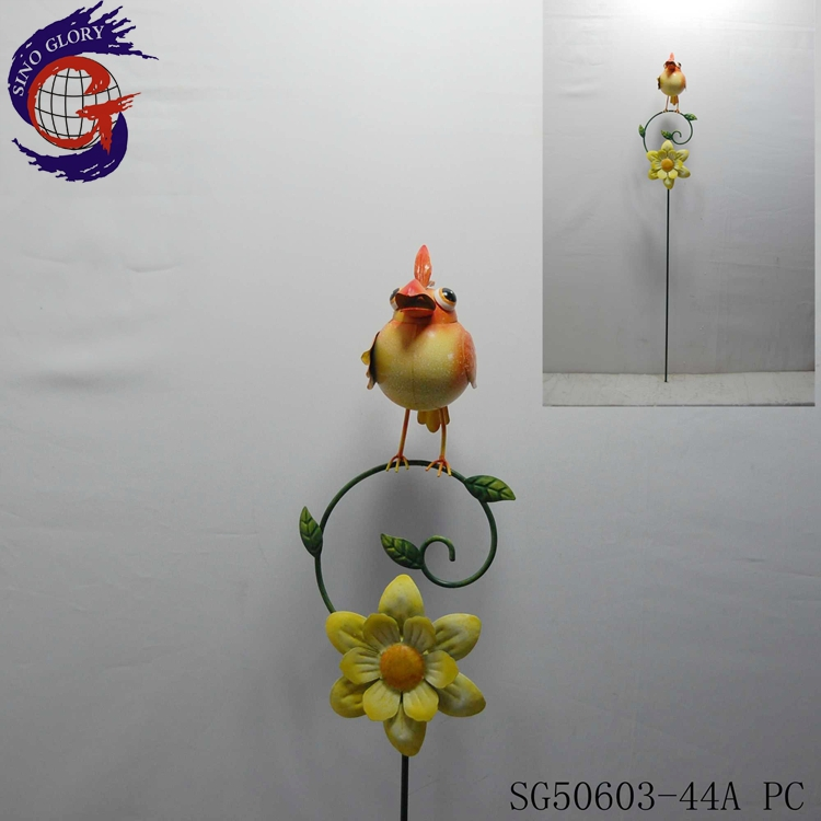 Shining metal bird standing on stick with metal garden decorative windmill