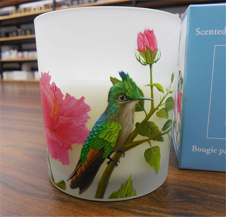 scented pillar candle with flower and bird pattern on the holder