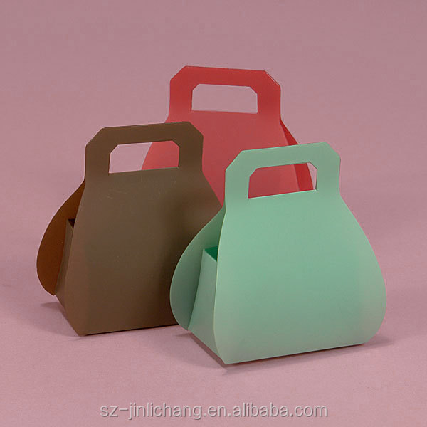 Small brightly colored purse shaped plastic package boxes