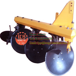 Agricultural tractor mounted disc plough in plowing land machine