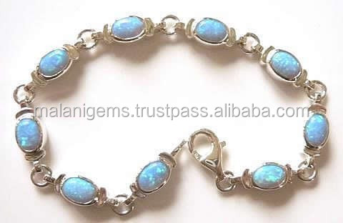 Seven and quarter inch long silver and synthetic blue opal bracelet. Set with nine 7x5mm, oval blue/turquoise lab created opals