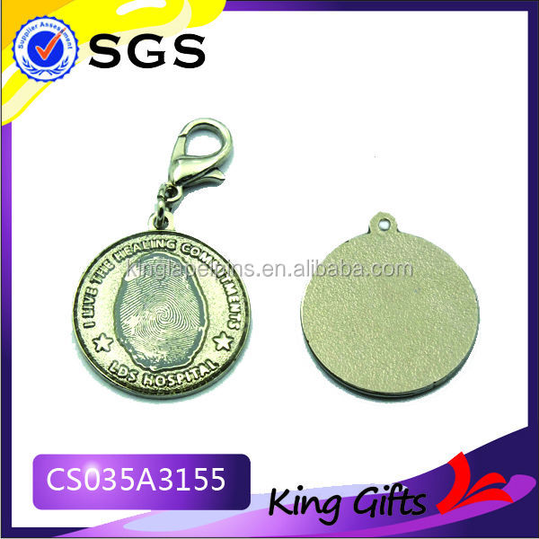 large round gold metal key chain with stamped logo
