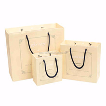 Wholesale custom yellow paper gift bags with logo gold hot stamping