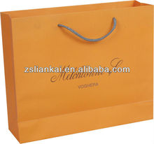 Bright orange large paper packaging shopping bags with nylon rope handles