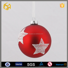 Red glass ball painted stars hanging on the Christmas tree