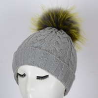 winter knit hat with large raccoon fur ball pom poms