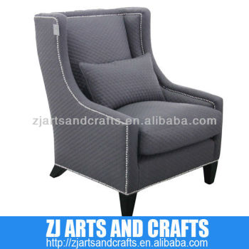 0473 modern sofa (Quilted charcoal linen arm chairr. With silver studs around arms and base with wenge finished legs.)