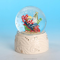 delicate Merry Christmas gift box inside snow globe dome