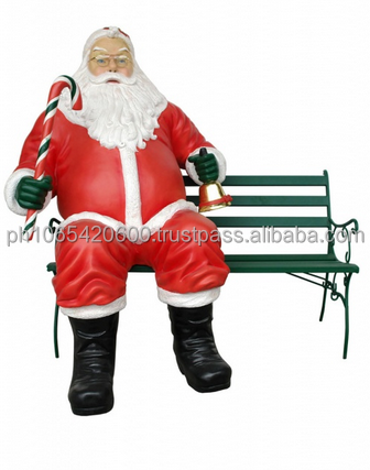 Santa Claus with Candy cane sitting on bench. ID:2996