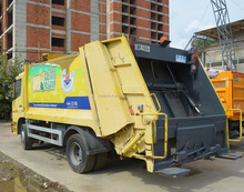 Used yellow waste collection truck