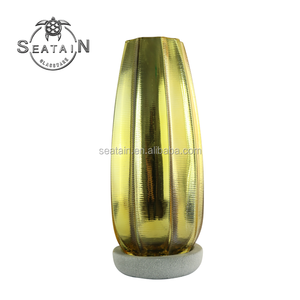 Golden glass vase for flowers or plants with a base