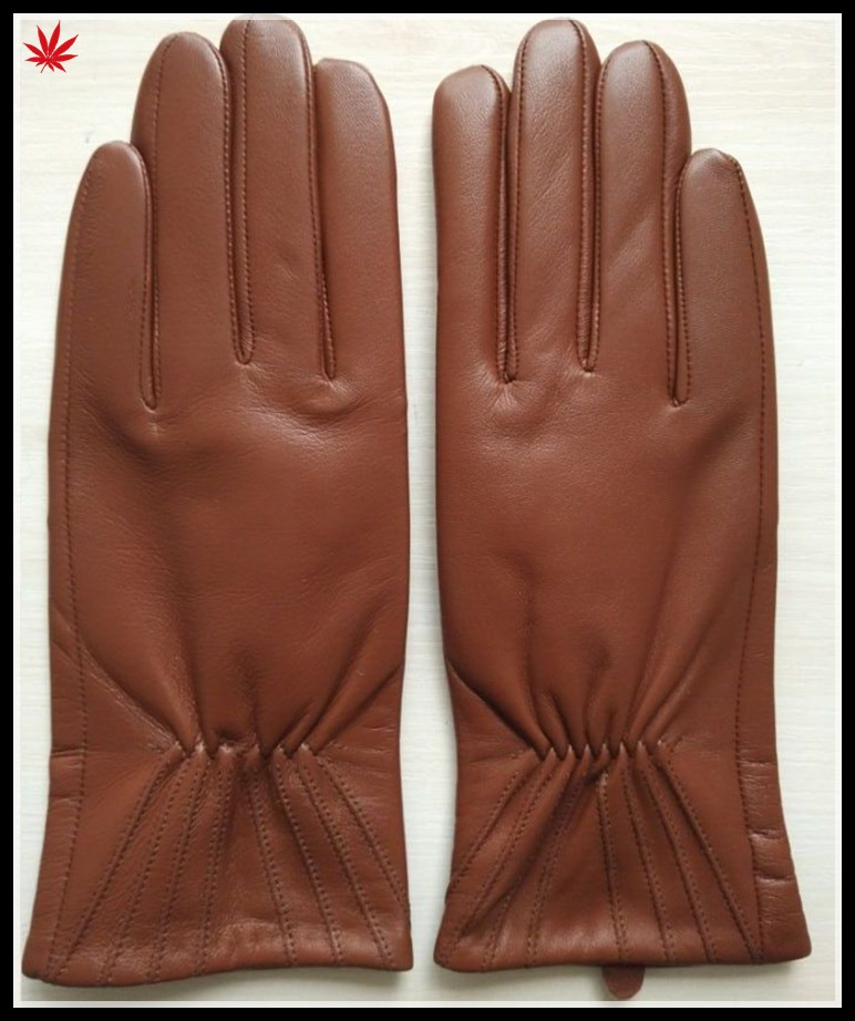 brown genuine leather hand gloves women putting on leather glove