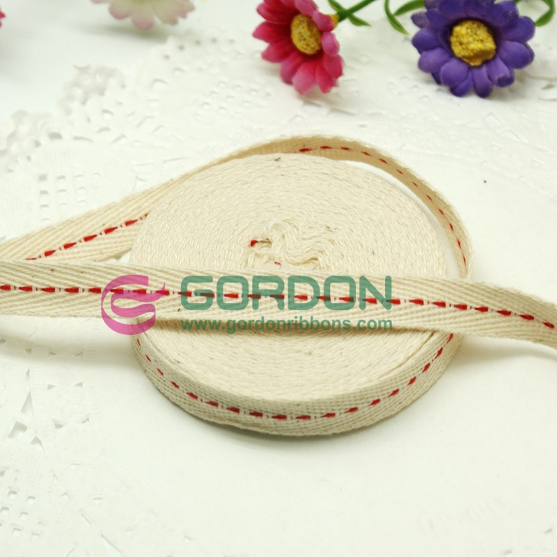 off white cotton ribbon with red stiched in the middle
