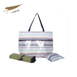 Paper straw material beach bag containing the mat and pillow