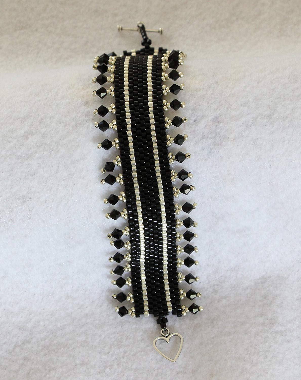 1166. Bead woven bracelet in silver and black glass beads with Swaroski crystal border and a toggle clasp.