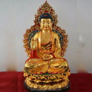 antique gold plated bronze buddha statue with a lotus flower