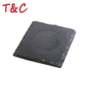 rough edged black stone slate cheese board food serving plates in kitchen