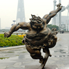 Bronze fat lady statue playing skate board in park