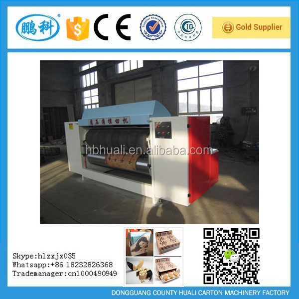 Computer-controlled cellular paperboard carton making machine with rotary cutter