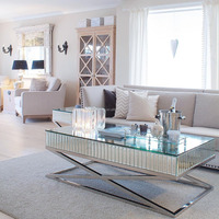 Cross based mirrored X style coffee table in stainless steel
