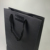 Eco friendly customized sizes black paper rope handle bags flat bottom printed kraft paper bag for clothes