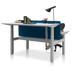 Face to face height adjustable desk base positioned back-to-back with cable collection