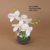 White artificial orchid with fake water and stone in glass pot