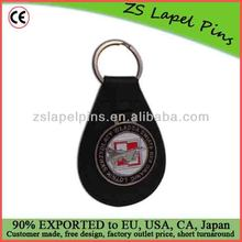 black leather key holder with metal enamel badge