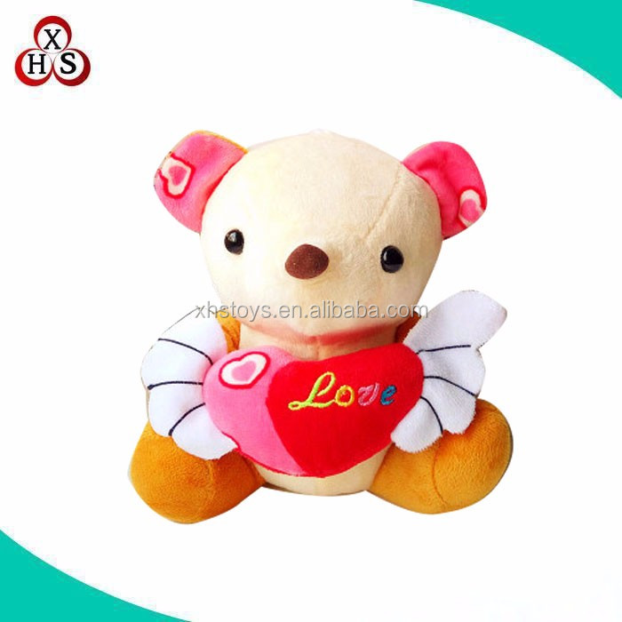 cute plush orange teddy bear with heart in front
